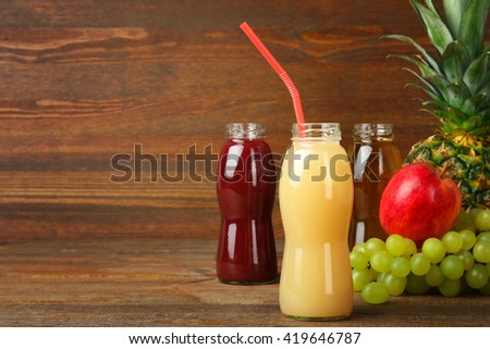 glass bottles of juice and an Apple with grapes and pineapple on the brown wooden background - stock photo