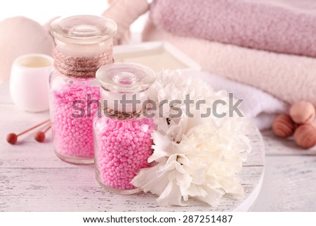 Glass bottles with color spa sea salt on wooden table, closeup - stock photo