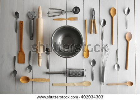 Glass bowl and kitchen cutlery on white table, top view - stock photo