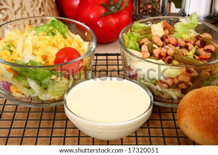 Glass bowl of black eye pea salad and garden salad with ranch dressing in kitchen or restaurant. - stock photo