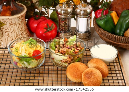 Glass bowl of black eye pea salad, garden salad and rolls in kitchen or restaurant. - stock photo
