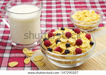 Glass bowl of cornflakes with berries and cup of milk on a red tablecloth - stock photo