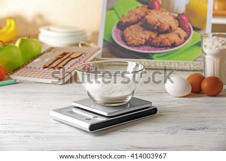 Glass bowl of sugar and digital kitchen scales on light wooden table - stock photo