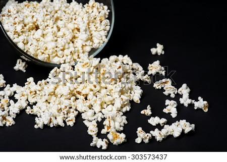 Glass bowl with popcorn on black background - stock photo