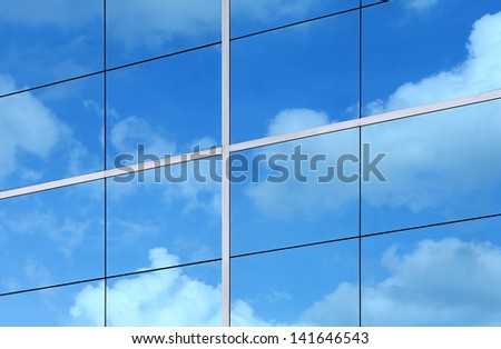 Glass building wall with reflection of clouds - stock photo