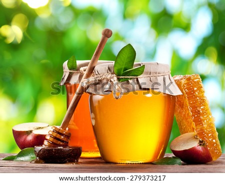 Glass cans full of honey and apples on old wooden table in the garden. - stock photo