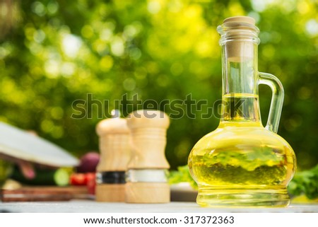 glass carafe with oil olive on the kitchen table - stock photo