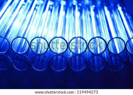 Glass chemistry tubes on a colour background - stock photo