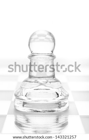 glass chess pawn is standing on board, cut out from white background - stock photo