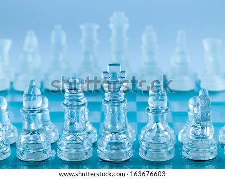 Glass Chess Pieces on a Frosted Glass Chessboard - stock photo