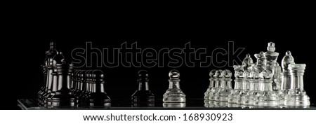 Glass Chess pieces on a glass chessboard on a black background - stock photo