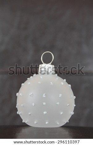 Glass christmas ball against leather and dark wood background - stock photo