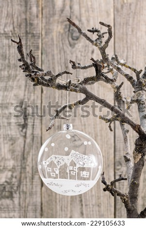 Glass Christmas ball hanging on bare branch over wooden background - stock photo