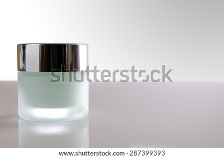 Glass closed jar with facial or body cream on white table. Front view. White isolated background - stock photo