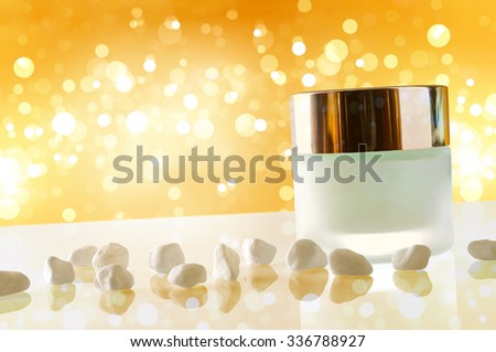Glass closed jar with facial or body moisturizer on white table with small white stones. Front view. Horizontal diagonal composition. Yellow bokeh background. - stock photo