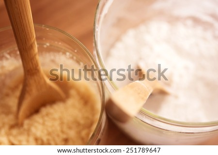 Glass container of brown sugar and flour with wooden spoon. Focus is on top edge of container. Shallow depth of field. - stock photo