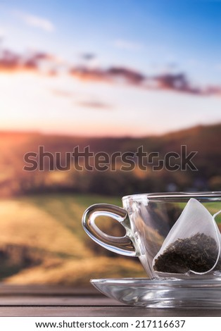 Glass cup and saucer with teabag and an amazing view of sunset - stock photo