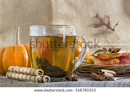 Glass cup of black tea with rolled wafers and dried fruits. - stock photo