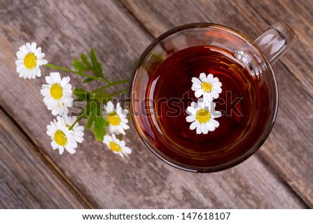 Glass cup of camomile tea with camomile flowers, on vintage wood table. - stock photo
