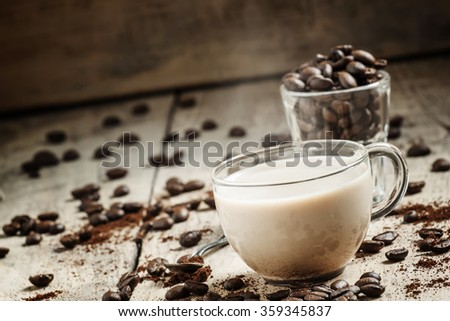 Glass cup of coffee with milk, spilled grain and ground coffee on the old wooden background in rustic style, selective focus - stock photo