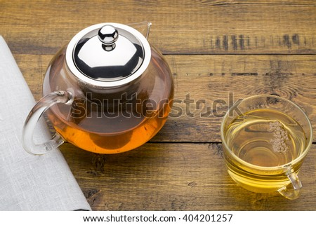 Glass cup of green tea and teapot - stock photo