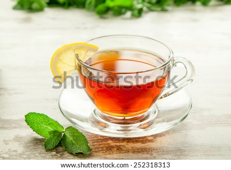 Glass cup of tea on a wooden table with lemon and mint leaves. - stock photo