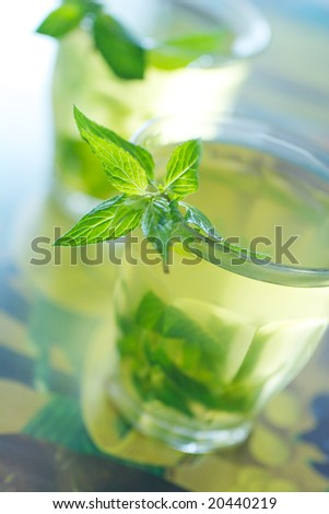 Glass cup of tea with a fresh mint on exotic background - stock photo