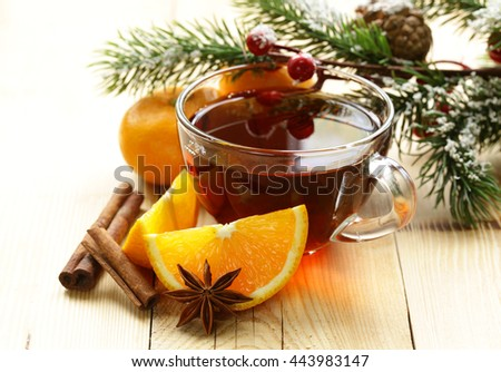 glass cup of tea with anise, cinnamon and citrus fruits winter drink, Christmas decorations - stock photo