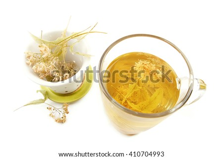 Glass cup of tea with lime dry blossom and strainer isolated on white. Linden decoction. - stock photo