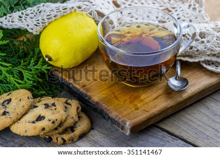 Glass cup of tea with mint. Homemade chocolate chip cookies, lemon, thuja branches on wooden background - stock photo