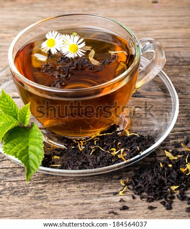 Glass Cup Tea with camomile flower and Mint Leaf, on brown wooden palette - stock photo