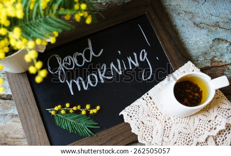 Glass cup with tea and blooming yellow mimosa with good morning note on wooden background - stock photo