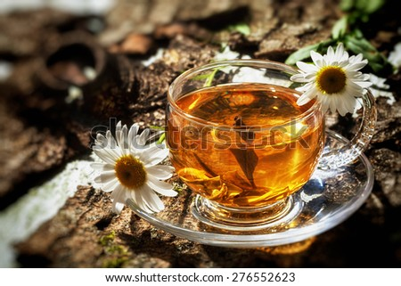 Glass cup with tea and daisy flower on old wooden table. - stock photo