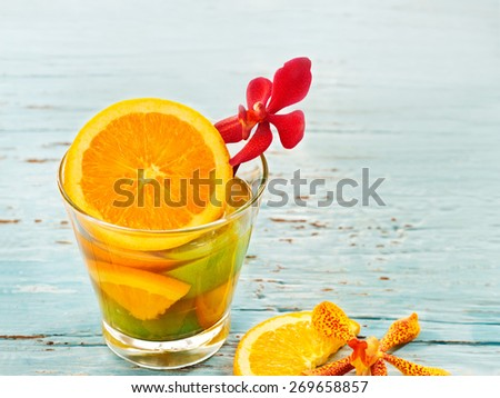 glass delicious refreshing drink of mix fruits orange and lemon on blue vintage wooden, infusioned water, soft focus - stock photo