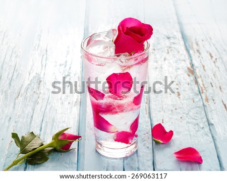 glass delicious refreshing drink of rose petal flower on blue wooden background, infusioned water  - stock photo