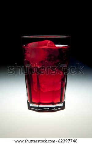 Glass filled with colored alcohol, black background. - stock photo
