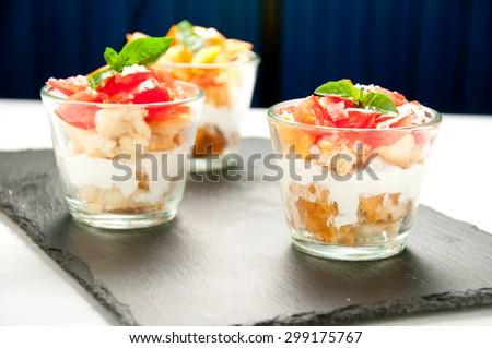 Glass filled with layers of frisella , buffalo mozzarella , tomato and basil - stock photo