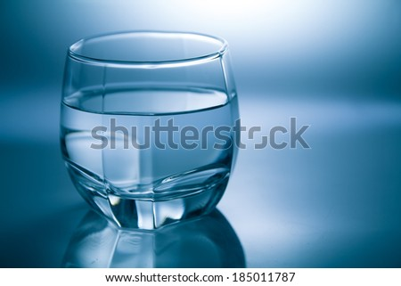 Glass filled with water isolated with reflection - stock photo