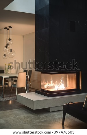 Glass fireplace with burning fire inside and a black chimney. On the background there is a table with flowers in vases, chairs and glass round lamps over them. Walls are light. On the floor there are - stock photo
