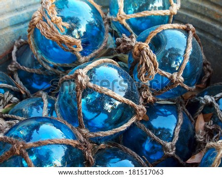 Glass fishing floats with rope knot netting piled in a bucket. - stock photo