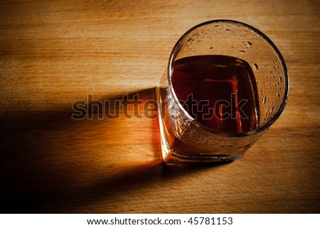 glass from whisky on a wooden table - stock photo