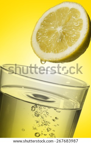 glass full of fresh water with lemon juice, on yellow background - stock photo