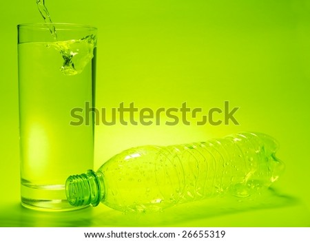 Glass full of water and empty bottle - stock photo