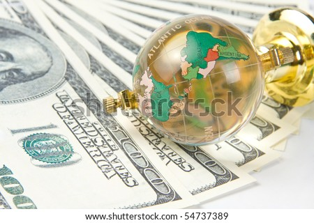 Glass globe and dollars - stock photo