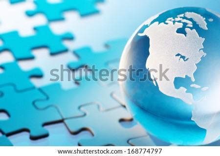 Glass globe and unfinished puzzle. Closeup of glass globe. Showing Americas.  - stock photo