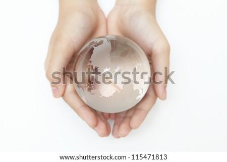 Glass globe in hand. - stock photo
