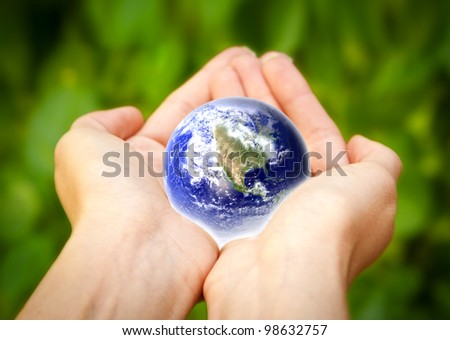 glass globe in hand. Elements of this image furnished by NASA - stock photo