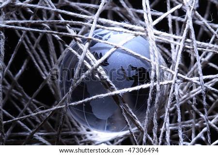 Glass globe inside gray crossing rope on dark background - stock photo