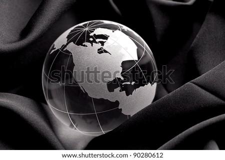 Glass globe on a silk cloth background - stock photo