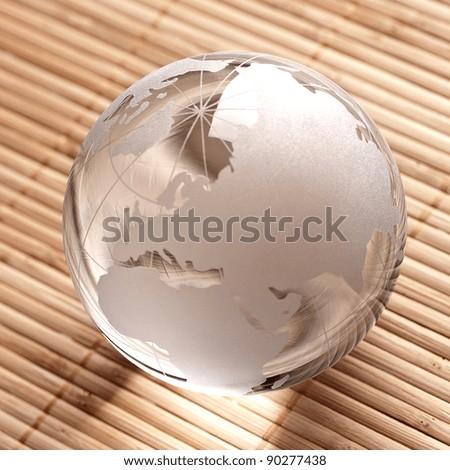 Glass globe on bamboo background - stock photo
